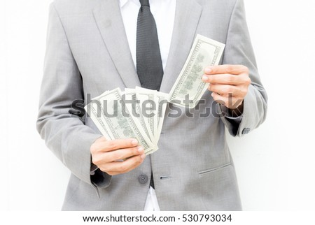 businessman giving cash dollars to the client,Concept of finance success. Man in a gray suit holds out hand with US dollars, Money and business topic: hand in a suit holding a banknote of 100 dollars