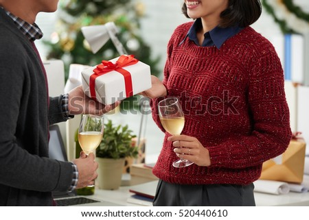 Businessman giving Christmas present to his female colleague