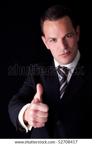 businessman giving consent, with thumb up, isolated on black background. Studio shot. - stock photo