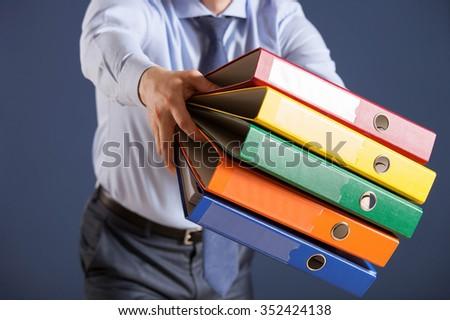 Businessman giving folders to you, closeup shot - stock photo