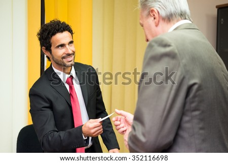 Businessman giving his business card to a customer  - stock photo