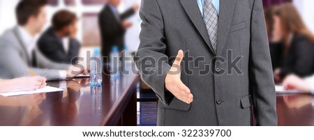Businessman giving his hand for a handshake and business people