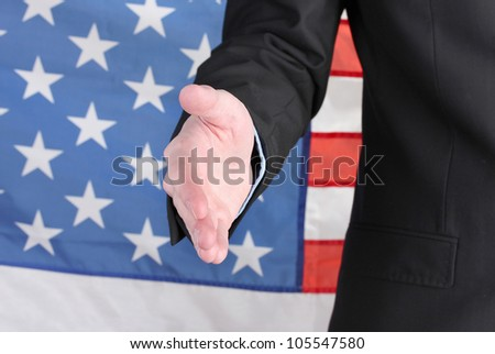 Businessman giving his hand for a handshake on American flag background