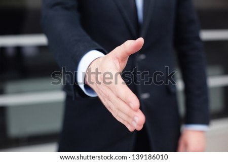 Businessman giving his hand for handshake - stock photo