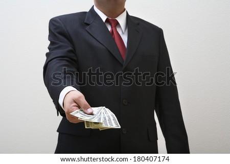Businessman giving money isolated on white - stock photo