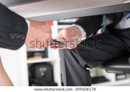 Businessman giving money under a table - stock photo