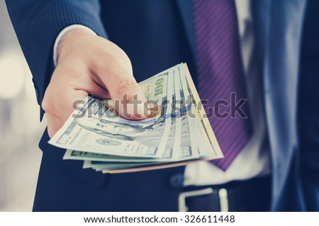 Businessman giving money, united states dollar (USD) bills - cash, payment and financial concepts - stock photo