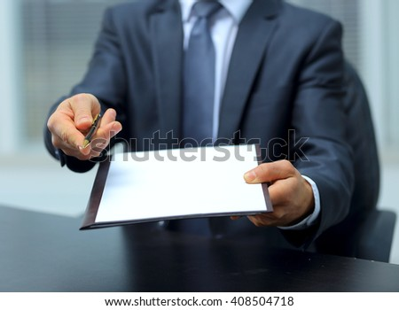 Businessman giving pen for your signature on clipboard - stock photo