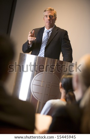 Businessman giving presentation at podium - stock photo