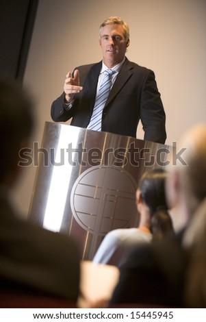 Businessman giving presentation at podium - stock photo