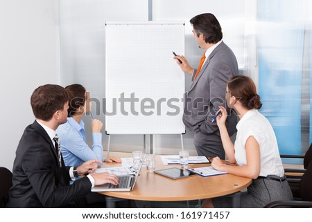 Businessman Giving Presentation To His Colleagues At Conference