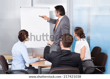Businessman Giving Presentation To His Colleagues At Conference - stock photo