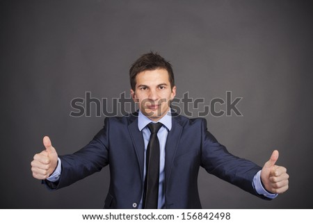 Businessman giving thumbs up - stock photo