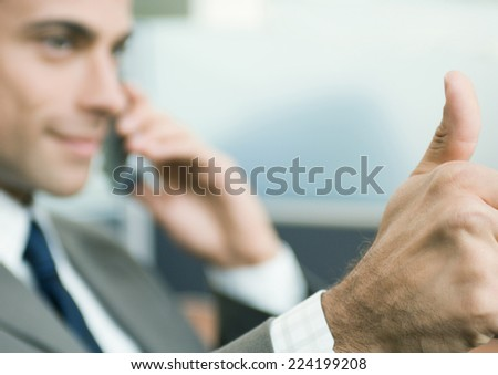 Businessman giving thumbs-up - stock photo