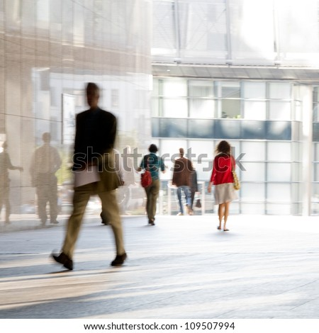 Businessman goes against the modern building. Blurred motion. - stock photo