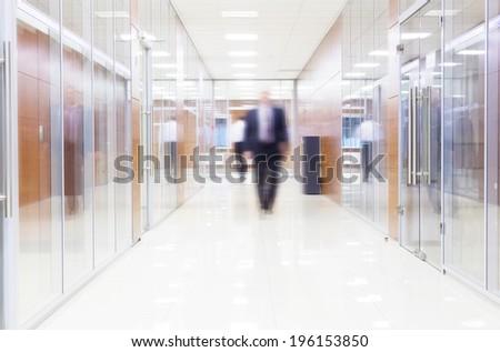 businessman goes along a corridor at modern office - stock photo