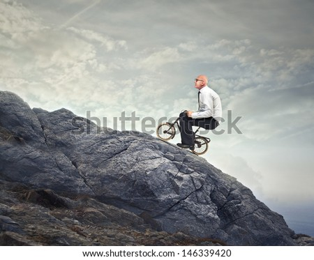 businessman goes with the bike on the rocks uphill - stock photo
