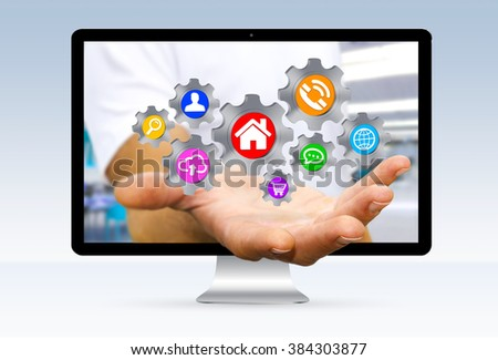 Businessman going out of a computer screen with colorful cogwheels icons flying over his hand