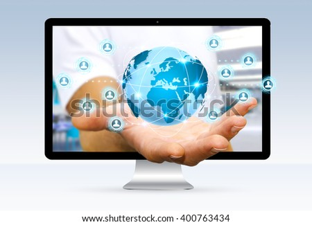 Businessman going out of a computer screen with digital world connected to his fingers