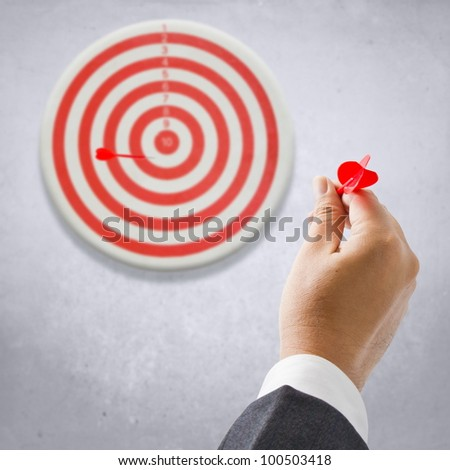 Businessman going to throw the dart to the target - stock photo