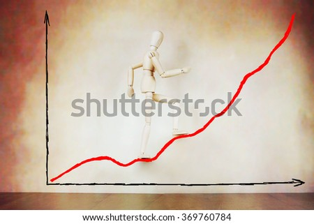 Businessman going up on rising graph. Abstract image with a wooden puppet - stock photo