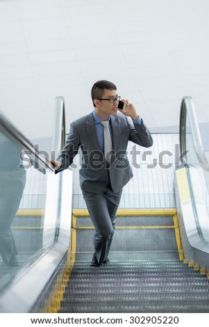 Businessman going up the escalator and calling on the phone