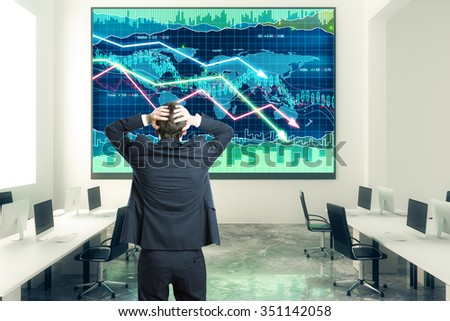 Businessman grabs the head in open space office with business chart at the wall - stock photo