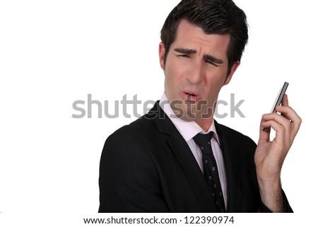 Businessman grimacing at his phone - stock photo