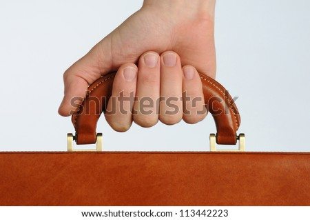 businessman gripping the handle of a brown leather briefcase