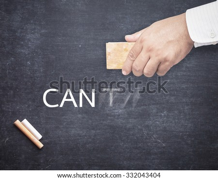Businessman hand changing the word cannot to can. Alphabet T being erased from a chalkboard. Change concept. - stock photo