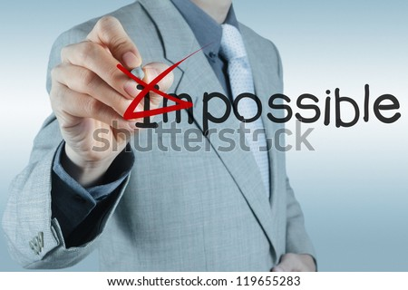 Businessman hand changing the word impossible into possible