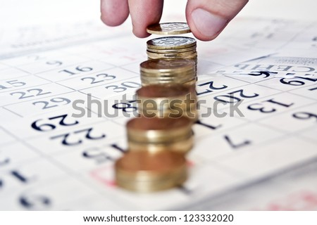 businessman hand coins in finger and row stacks them - stock photo