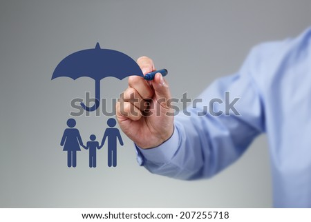 Businessman hand drawing an umbrella above a family concept for protection, security, finance and insurance - stock photo