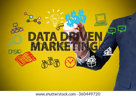 businessman hand drawing and writing DATA DRIVEN MARKETING on yellow background , business concept , business idea - stock photo