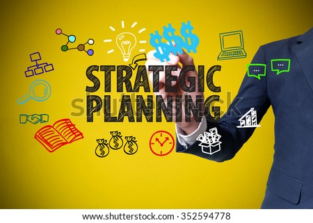 businessman hand drawing and writing STRATEGIC PLANNING on yellow background , business concept , business idea - stock photo