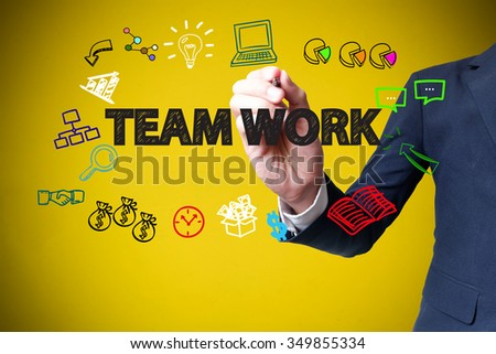 businessman hand drawing and writing TEAM WORK on yellow background , business concept , business idea - stock photo