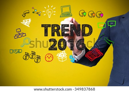 businessman hand drawing and writing TREND 2016 on yellow background , business concept , business idea - stock photo