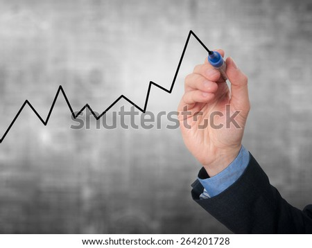 Businessman hand drawing graph of growth. Isolated on grey background. Stock Image - stock photo