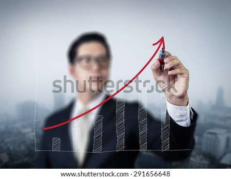 Businessman hand drawing graph of growth, new business in the city collection, studio shot