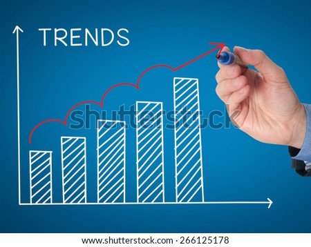 Businessman hand drawing growth trends chart isolated on blue background. Stock Image - stock photo