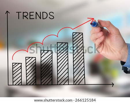 Businessman hand drawing growth trends chart isolated on office background. Stock Image - stock photo