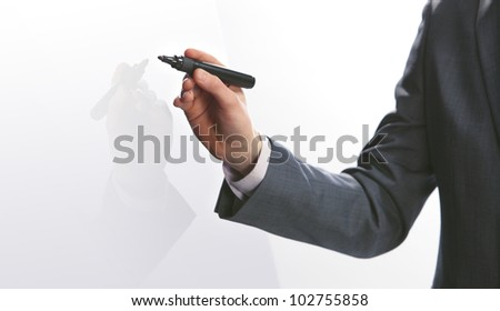 Businessman hand drawing in a whiteboard, copy space - stock photo