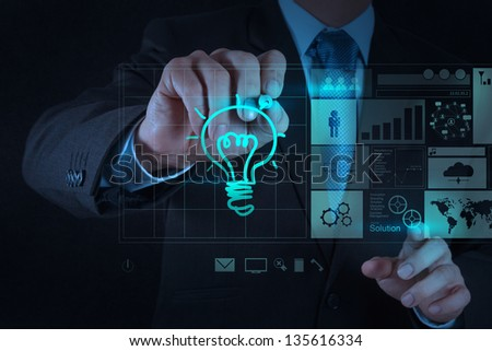 businessman hand draws lightbulb with new computer interface as strategy business concept