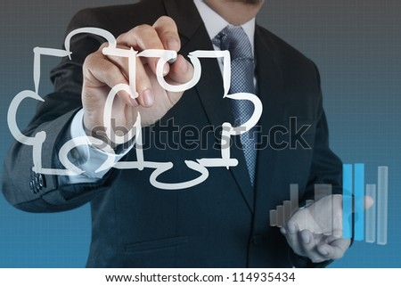 businessman hand draws puzzles as partnership concept - stock photo