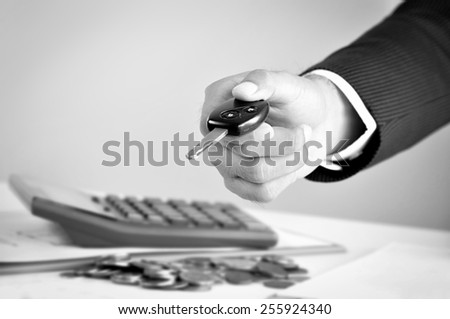 Businessman hand giving a car key, car rental & pawn concepts - black & white tone - stock photo