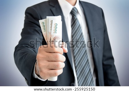 Businessman hand grabbing money - Thai Baht (THB)