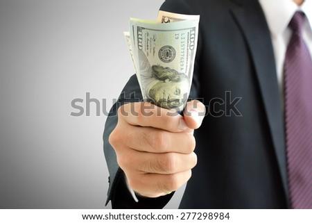 Businessman hand grabbing money, US dollar (USD) bills - stock photo