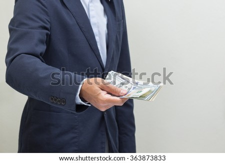 Businessman hand grabbing US dollar banknote, USD