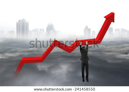 businessman hand hanging on red trend chart with gray cloudy sky cityscape background - stock photo