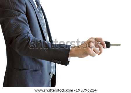 Businessman hand holding a car key - unlock action - on white background - stock photo